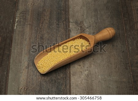 millet in a scoop on a wooden table - stock photo