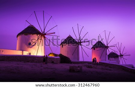 Mills on the Greek island in the sunset - stock photo