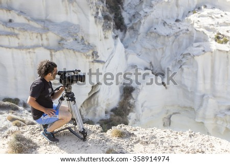 Milos, Greece - September 11, 2015: Nature photographer with digital camcorder on top of the mountain  - stock photo