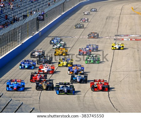 Milwaukee Wisconsin, USA - July 12, 2015: Verizon Indycar Series Indyfest ABC 250 Milwaukee Mile. Cloud of dust, smoke, green flag Indy car racing.  Indy racecars vying for position side by side start