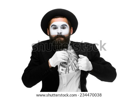 mime as a businessman in a  suit putting money in his pocket. isolated on a white background. concept  love of money and  greed - stock photo