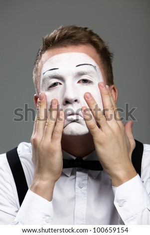 Mime face and hands in a theatrical make-up isolated on gray background - stock photo