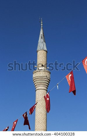 Minaret of a mosque in Bodrum, Turkey, against a blue sky with flags of Turkey in foreground - stock photo