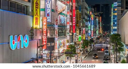 Minato Ward, Tokyo, Japan - August 13, 2017: Panoramic view of nightlife scene, people walking in colorful Streets shops and Billboards in Shinbashi district at night