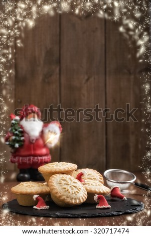 Mince pies on slate tray decorated with santa hats