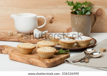 Mince Pies. Traditional Christmas Food. Olive Tree Board. Silver Spoons. Decorations. Wooden Table. - stock photo