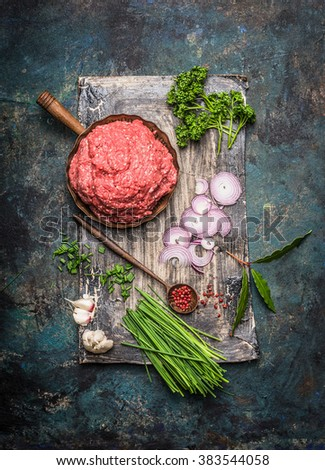 Minced meat  in frying pan with cooking ingredients and wooden spoon on dark rustic background, top view - stock photo