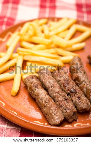 Minced meat kebabs and french fries.