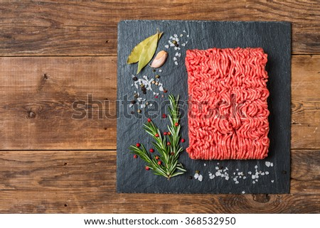 Minced meat on a slate stone black board with seasonings and fresh rosemary on wooden background, top view - stock photo
