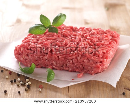 Minced meat on butcher paper with basil and pepper, selective focus - stock photo