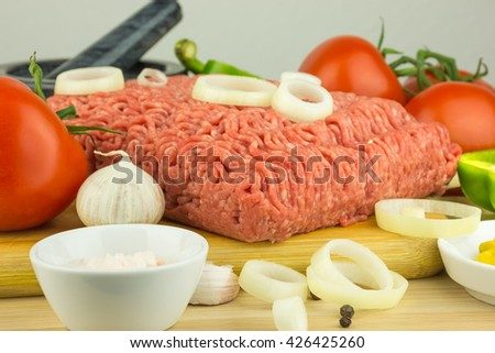 Minced meat on cutting board and vegetables on wooden background