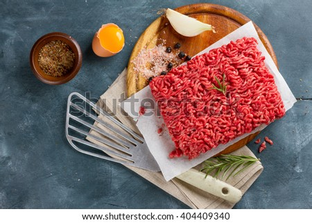 Minced meat on cutting board with spices, spatula and egg, selective focus - stock photo