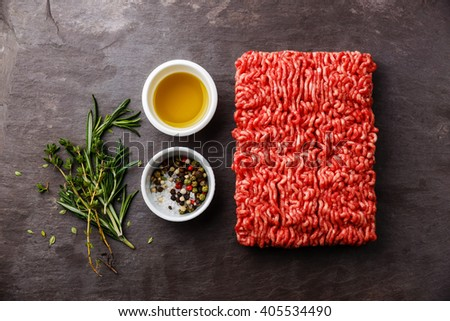 Minced meat on stone slate background with pepper, oil and herbs - stock photo