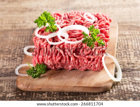 minced meat with onion on wooden board - stock photo