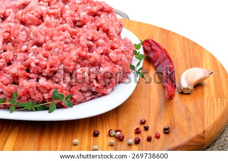 minced meat with pepper, thyme and garlic on cutting board isolated on white - stock photo