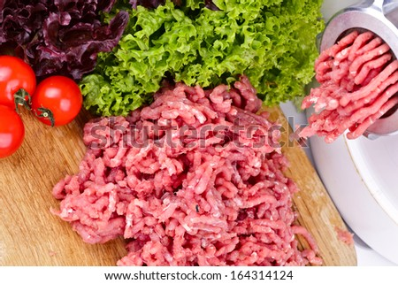Mincer with fresh chopped meat - stock photo