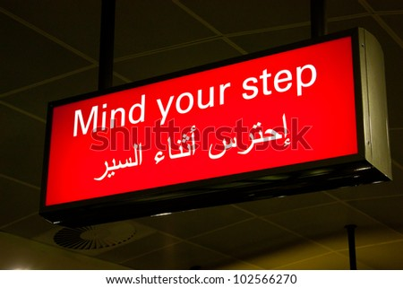 Mind your step sign in an international airport in Middle East with Arabic information - stock photo