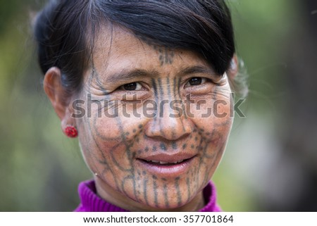 MINDAT, MYANMAR - DECEMBER 7: Chin tribe tattoed woman (Muun) poses for a photo on December 7, 2015 Mindat, Myanmar. Chin people, also known as the Kukis are a number of Tibeto-Burman tribal people.