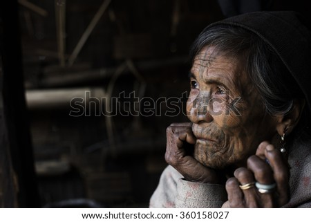 MINDAT, MYANMAR - DECEMBER 8: Chin tribe tattooed woman (Muun) poses for a photo on December 8, 2015 Mindat, Myanmar. Chin people, also known as the Kukis are a number of Tibeto-Burman tribal people.