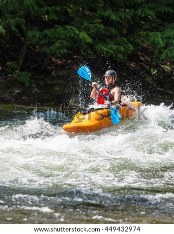 Minden, Ontario - July 5, 2016: White water kayak paddler steering his boat through the rough rapids on Gull River at the Minden Whitewater Preserve - stock photo