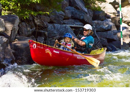 MINDEN, ONTARIO - SEPTEMBER 8: An unidentified contestant and his child compete at 2013 Open Canoe Slalom Race at Gull River in Minden, Ontario, Canada on September 8, 2013.
