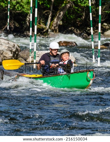 MINDEN, ONTARIO - SEPTEMBER 6, 2014: Father and son paddling at 2014 Open Canoe Slalom Race at Gull River in Minden, Ontario, Canada. - stock photo