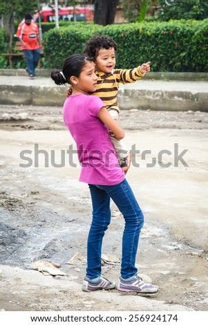 MINDO, ECUADOR - JAN 1, 2015: Unidentified Ecuadorian girl plays with her little brother. 71,9% of Ecuadorian people belong to the Mestizo ethnic group