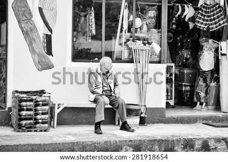 MINDO, ECUADOR - JAN 1, 2015: Unidentified Ecuadorian man sits near a shop. 71,9% of Ecuadorian people belong to the Mestizo ethnic group