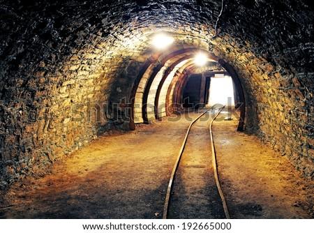 Mine underground tunnel with railroad - stock photo