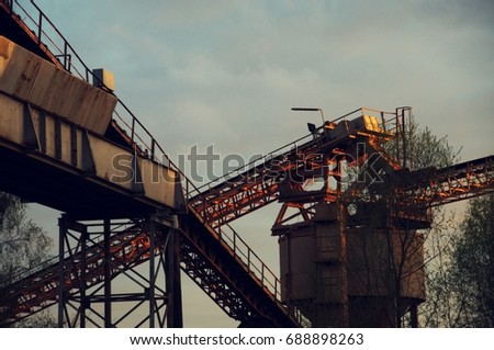 Mine with construction crane and conveyor belt at sunset