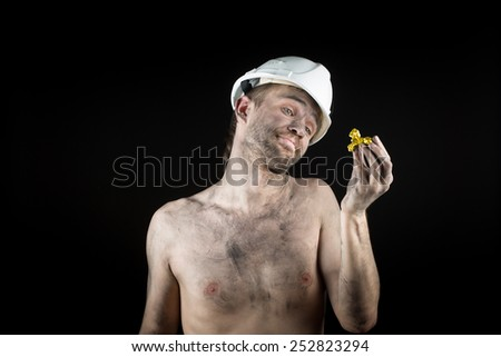 miner shows a golden nugget  - stock photo