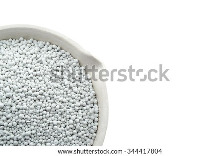 Mineral fertilizers in a chemical porcelain cup, isolated on the white background - stock photo