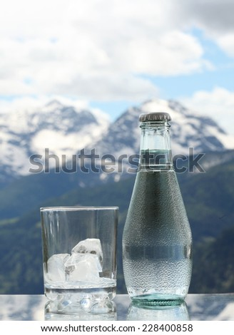 Mineral water bottle and glass with ice cubes, Alps mountains on the background