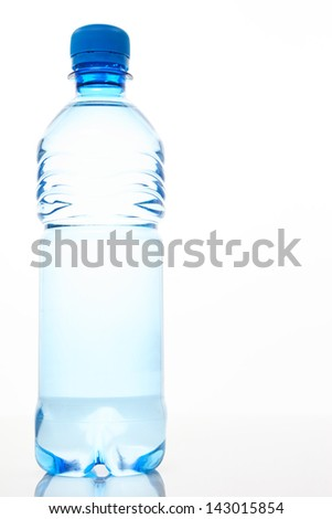 Mineral water in a bottle with a blue cap over a plain reflective surface with copy space on the right side.