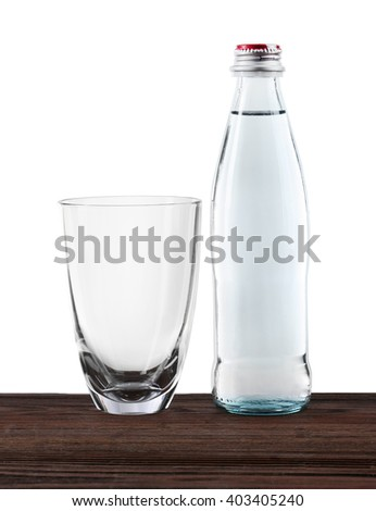 Mineral water in bottle and clean glass on wooden table on grey background - stock photo