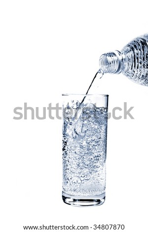 Mineral water pouring from bottle into a glass