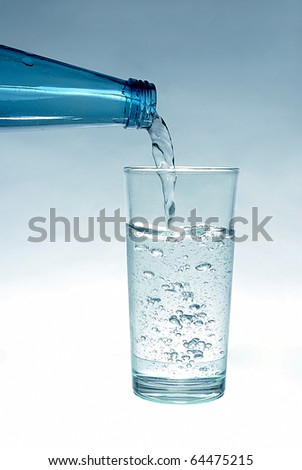 Mineral water pouring in a glass
