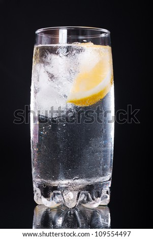 Mineral water with ice and lemon in a glass on a black background