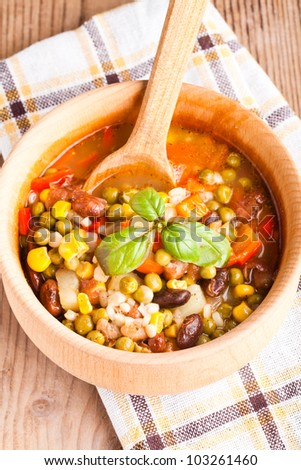 Minestrone soup in wooden bowl closeup. Traditional italian dish - stock photo