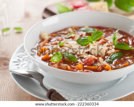 Minestrone soup with cheese and basil, selective focus - stock photo