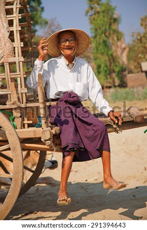Mingun, Myanmar - February 28, 2011 : Very old burmese man sitting on his cart in the sands of Mingun bay in the morning