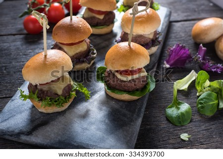 mini beef burgers,party food on wooden table - stock photo