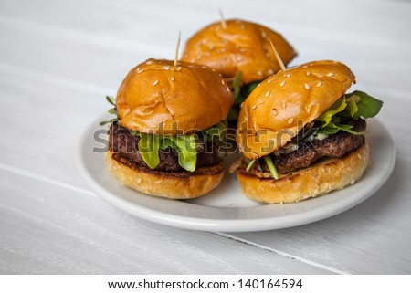 Mini Beef Sliders with Arugula on Sesame Seed Buns on a White Washed Wood Background - stock photo