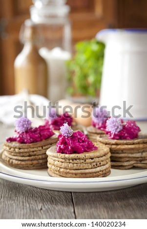 Mini buckwheat pancakes garnished with colorful beet salad and chives blossoms - stock photo
