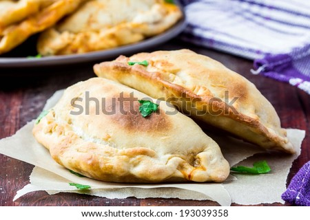 Mini calzone, closed pizza, Italian pastry stuffed with cheese, meat, tomato sauce, tasty dish - stock photo