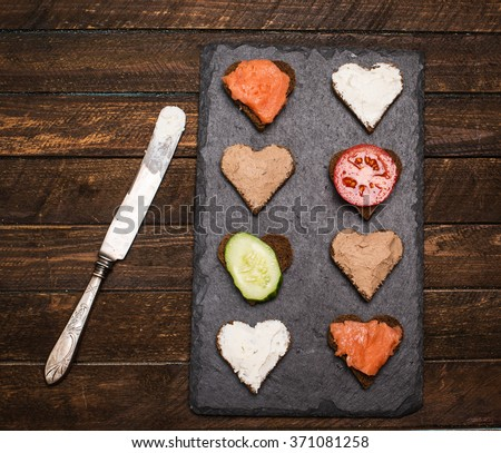 Mini canapes heart shape with different toppings on black slate board and vintage knife on rustic wooden background. Delicious appetizers. - stock photo