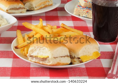 Mini cheeseburgers and fries on a picnic table loaded with food