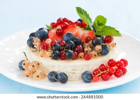 mini cheesecake with fresh berries on a blue background, close-up, horizontal - stock photo