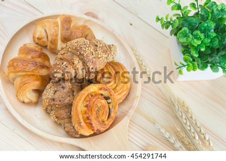 Mini croissant sesame and Mini croissant ham on wood table for breakfast - stock photo