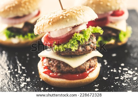 Mini double burgers appetizer, vintage look food. - stock photo